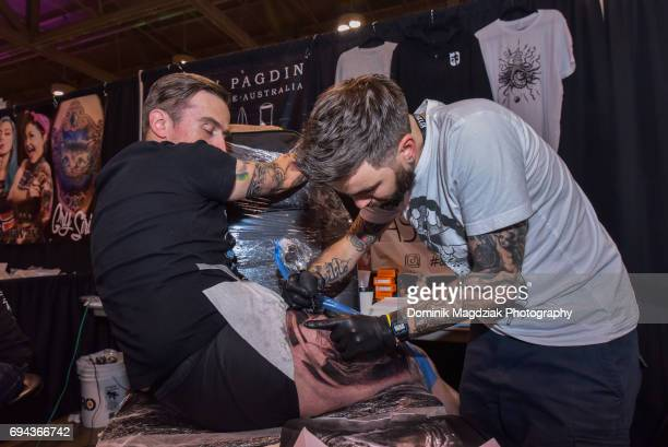 """English tattoo artist Ash Lewis tattoos a man during day one of the """"19th Annual Northern Ink Xposure Tattoo Convention"""" at the Metro Toronto..."""
