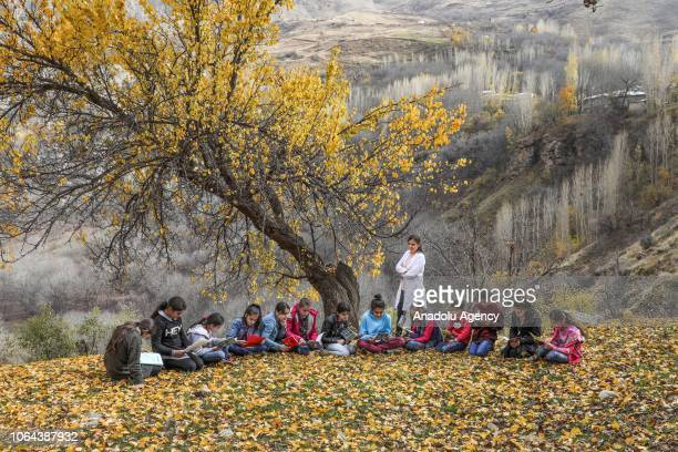 English teacher Aynur Korkmaz is seen with her students among the yellowish leaves during their lesson at the garden of the Alacayar Secondary School...