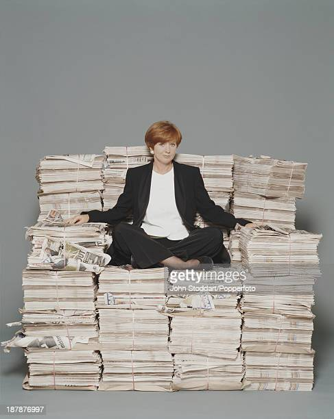 English television presenter Anne Robinson sits on top of a stack of bound newspapers circa 1992