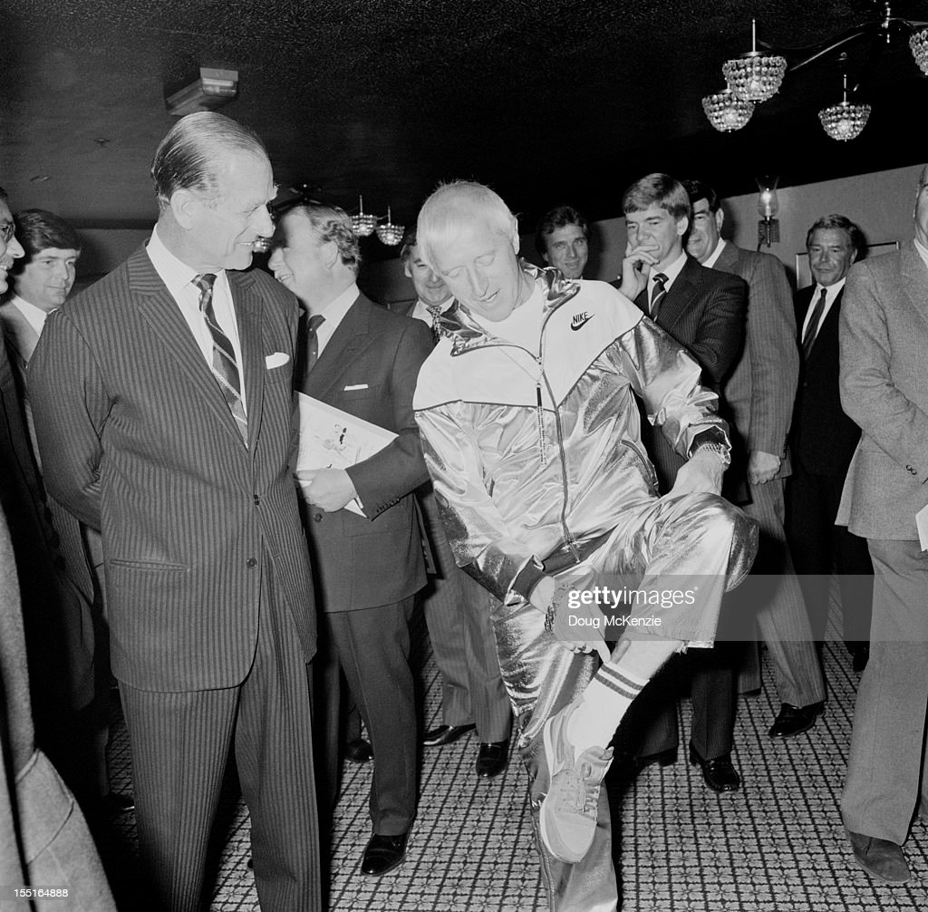 English television presenter Jimmy Savile (1926 - 2011) shows the Duke of Edinburgh a cigar which he keeps tucked into his sock, circa 1985.