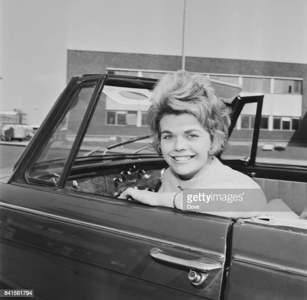 English television presenter Judith Chalmers smiles from a convertible car at Heathrow Airport UK 13th April 1964