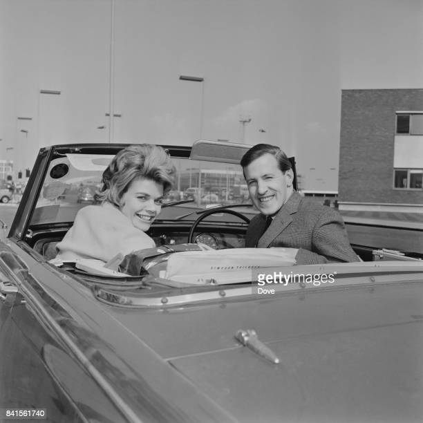 English television presenter Judith Chalmers with her husband English sports commentator Neil DurdenSmith on a convertible car at Heathrow Airport...