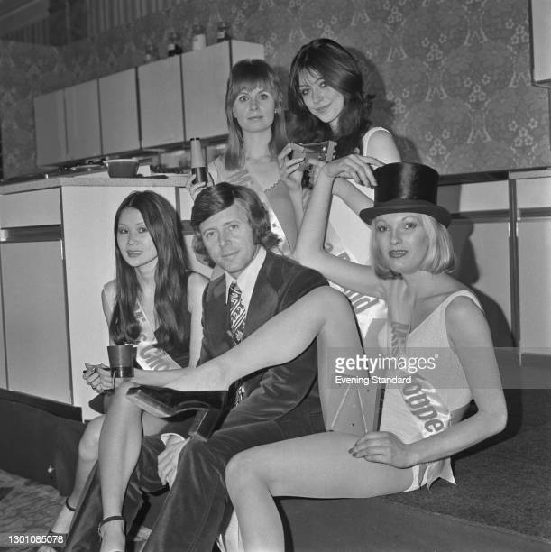 English television presenter Michael Aspel with four young actresses and models, advertising a new range of kitchen gadgets, UK, 5th March 1973. From...