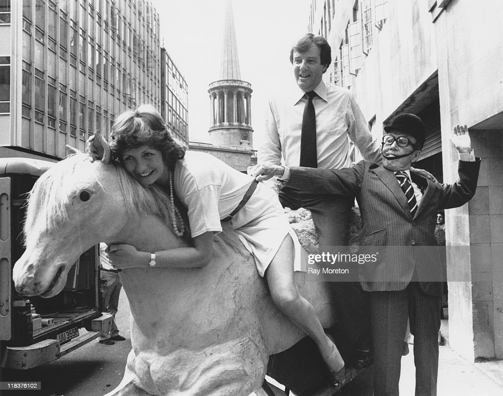 English television presenters Russell Harty (1934 - 1988) and Sue Lawley try out a mechanical horse outside Broadcasting House in London, with the help of comedian Arthur Askey (1900 - 1982), 4th June 1980.
