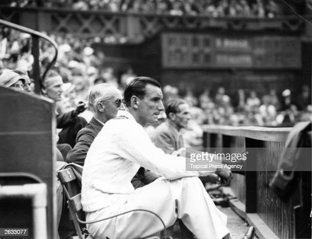 English tennis champion Fred Perry watches the match between Donald Budge and Bunny Austin at the All England Lawn Tennis Championships at Wimbledon...