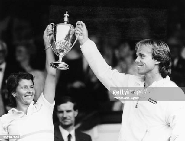 English tennis player John Lloyd and Australian tennis player Wendy Turnbull pictured smiling as they hold up their trophy in the Royal Box after...