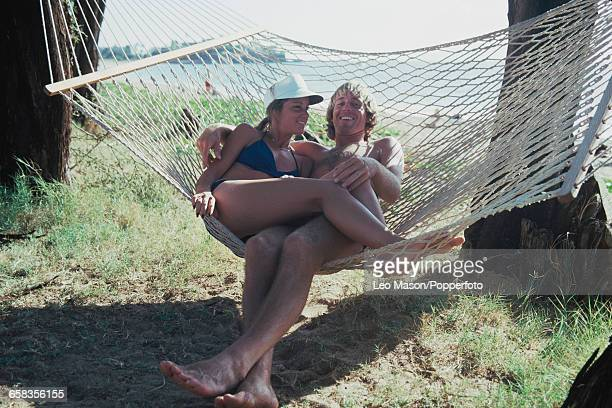 English tennis player John Lloyd and his partner and future wife American tennis player Chris Evert pictured lying together in a hammock beside a...