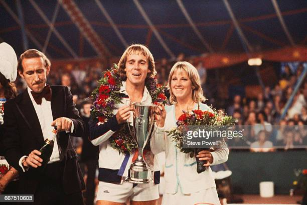 English tennis player John Lloyd and his wife American tennis player Chris EvertLloyd hold the trophy after the pair won the Love Doubles charity...