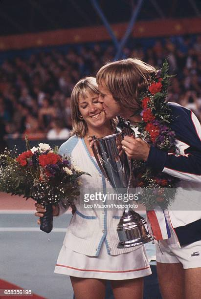 English tennis player John Lloyd kisses his wife American tennis player Chris Evert as he holds the trophy after the pair won the Love Doubles...