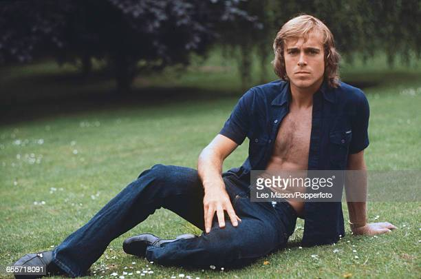 English tennis player John Lloyd posed wearing an unbuttoned dark blue shirt and jeans in 1977