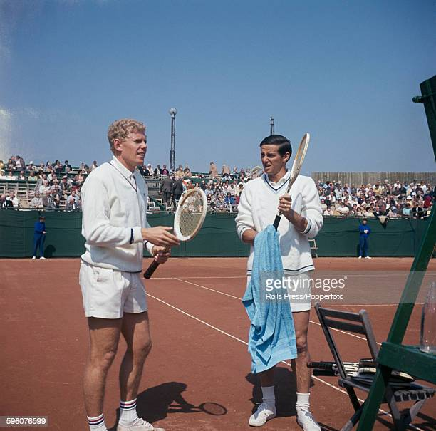 English tennis player Mark Cox stands with Australian tennis player Roy Emerson prior to their quarter final match at the 1968 British Hard Court...