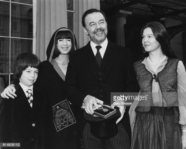 English theatre director Sir Peter Hall receives his knighthood at Buckingham Palace in London, accompanied by his second wife Jacqueline Taylor,...