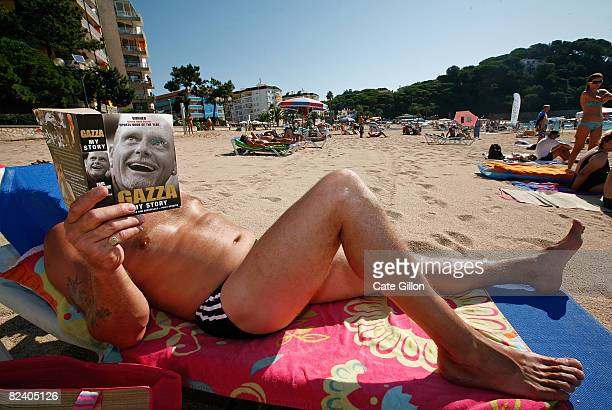 English tourist from Oxfordshire reads Gazza the book while relaxing on Fenals beach on August 18 2008 in Lloret de Mar Spain Feeling the pinch from...