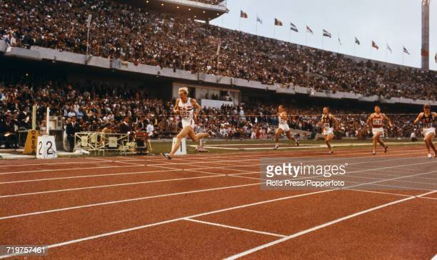 English track and field athlete David Hemery crosses the finish line in first place in a world record time to win the gold medal in the Men's 400...