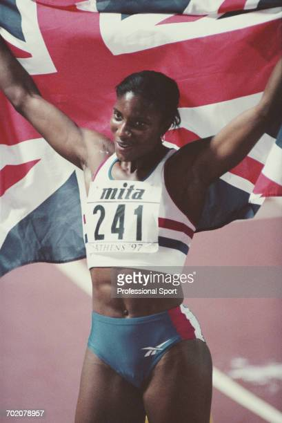 English track and field athlete Denise Lewis holds up the union jack national flag after finishing in 2nd place to win the silver medal in the...