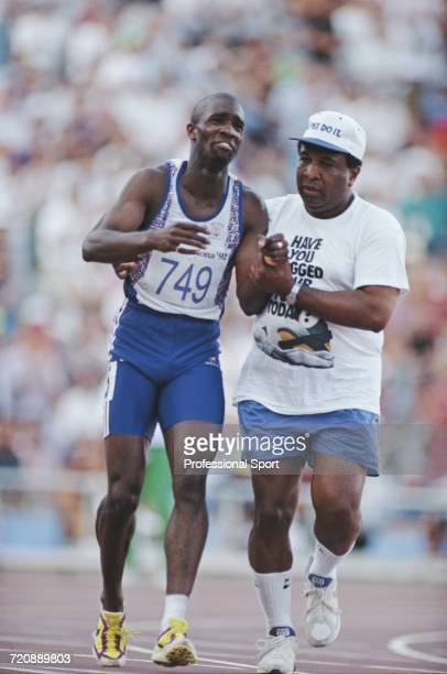 English track athlete Derek Redmond of the Great Britain team is aided by his father Jim Redmond to complete a full lap of the track after tearing...