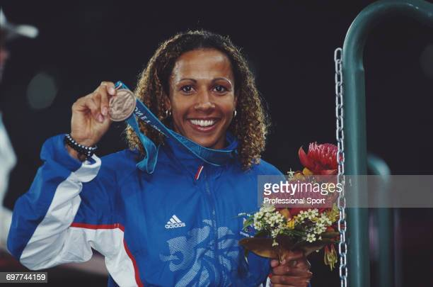 English track athlete Kelly Holmes holds up her bronze medal during the medal ceremony after crossing the finish line in third place for the Great...