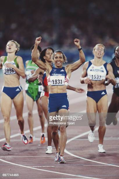 English track athlete Kelly Holmes raises her arms in the air in celebration as she crosses the finish line in third place for the Great Britain team...