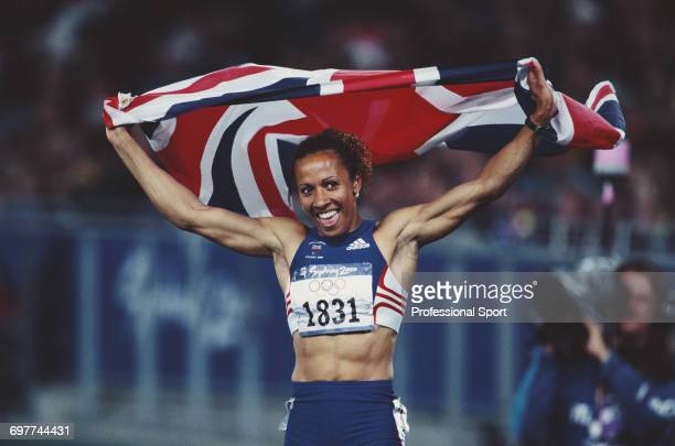 English track athlete Kelly Holmes raises her arms in the air to hold a union jack flag in celebration after crossing the finish line in third place...