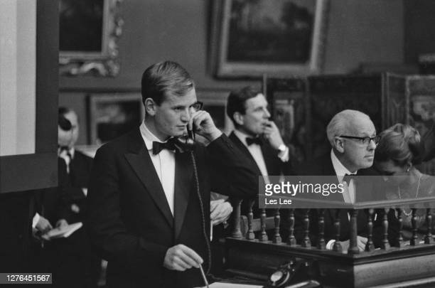 English travel writer Bruce Chatwin an employee of Sotheby's auction house in London pictured during the sale of a Cézanne painting for a record...