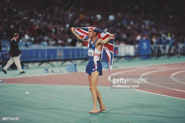 English triple jumper Jonathan Edwards holds a union jack flag up in the air in celebration after winning the gold medal for Great Britain in the...