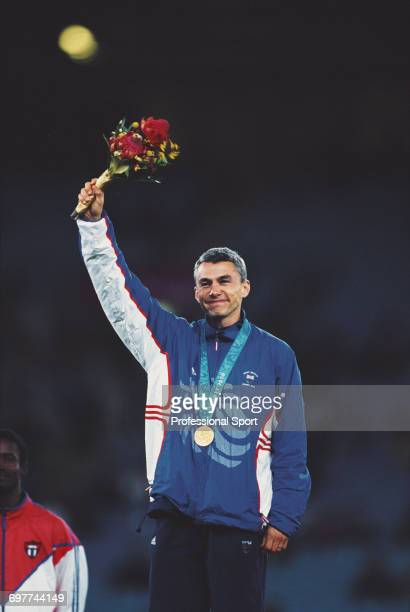 English triple jumper Jonathan Edwards raises one arm in the air in celebration on the medal podium after winning the gold medal for Great Britain in...