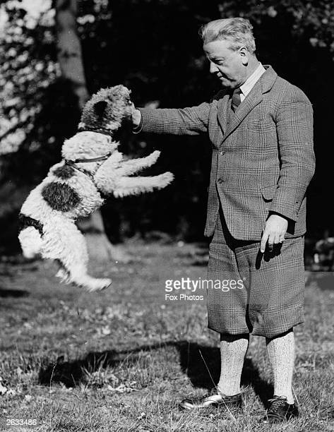 English violinist and composer Haydn Wood playing with his dog Pete in the garden of his London home