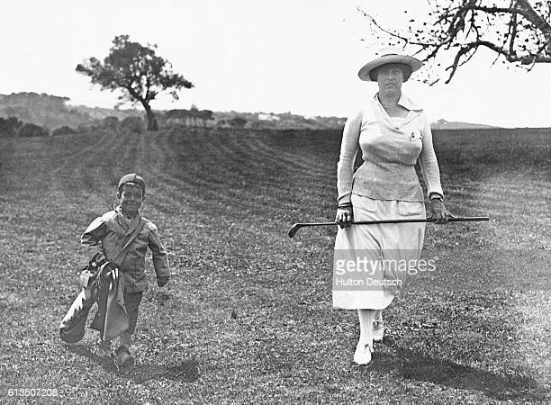 English woman Mrs Hugh Raynor golfs at the Algiers Golf Club with a four year old Algerian caddie who is also the club's mascot