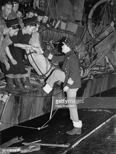 English writer actor and director Noël Coward embarks on the 'HMS Torrin' during the filming of the naval drama 'In Which We Serve' at Denham Studios...