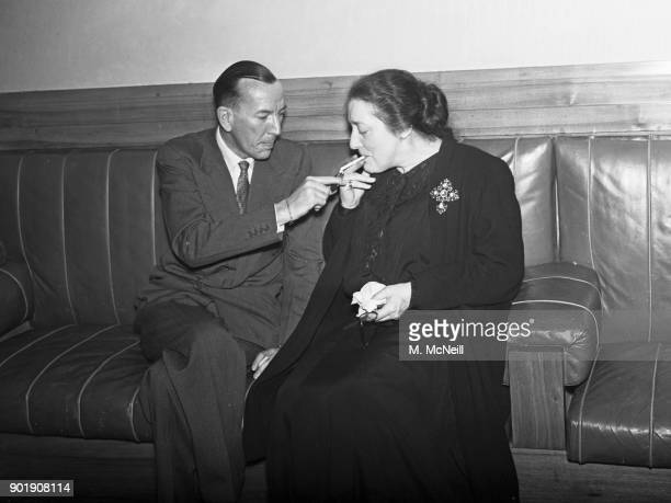 English writer actor and director Noël Coward lights a cigarette for actress Eva Moore at the Saville Theatre in London during the AGM of the Actors'...