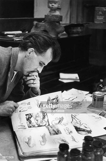 English writer and artist Mervyn Peake looking over some sketches Original Publication Picture Post 4276 An Artist Makes A Living pub 1946