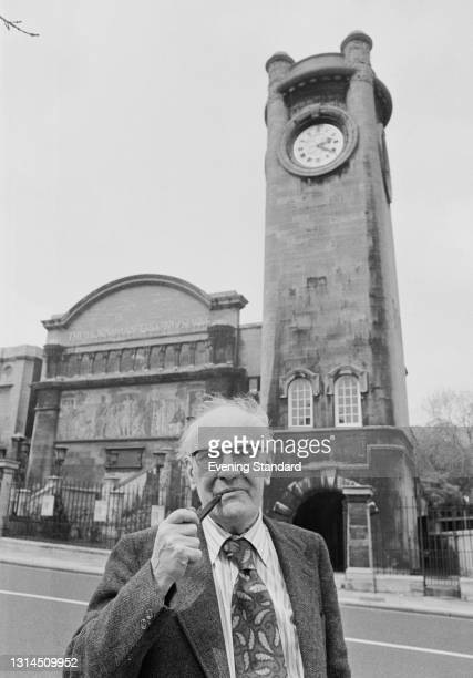 English writer and critic V. S. Pritchett, full name Victor Sawdon Pritchett smoking a pipe outside the Horniman Museum in Forest Hill, London, UK,...