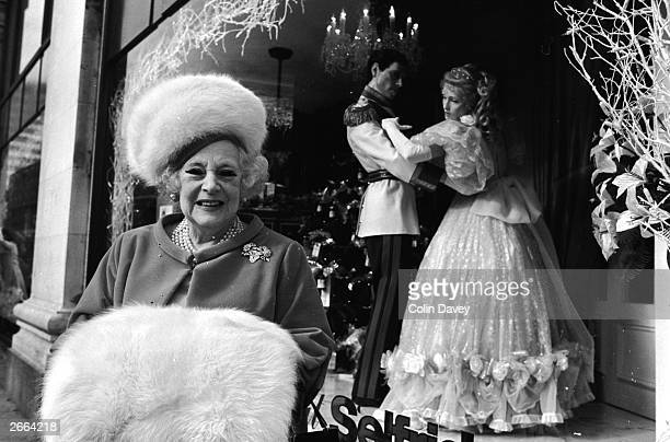 English writer Barbara Cartland with a large fur muff in front of her window display at Selfridges, London.