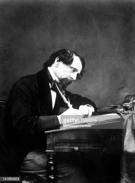 English writer Charles Dickens writing at his desk 1860s