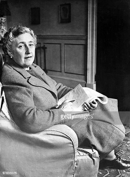 English writer Dame Agatha Christie poses in March 1946 for a photographer holding a notebook in her home Greenway House in Devonshire Agatha...