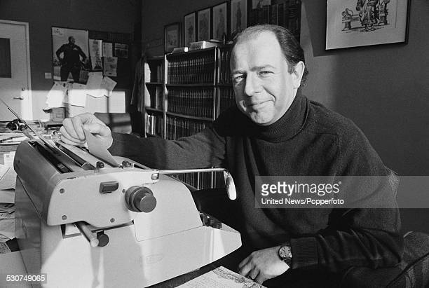 English writer satirist and editor of Punch magazine Alan Coren pictured sitting at a typewriter in the magazine's office in London on 21st Novenber...