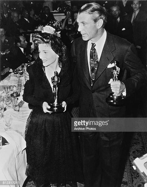 English-American actress, Joan Fontaine holding her 'Best Actress' Oscar for her role in 'Suspicion', and American film actor, Gary Cooper, with his...