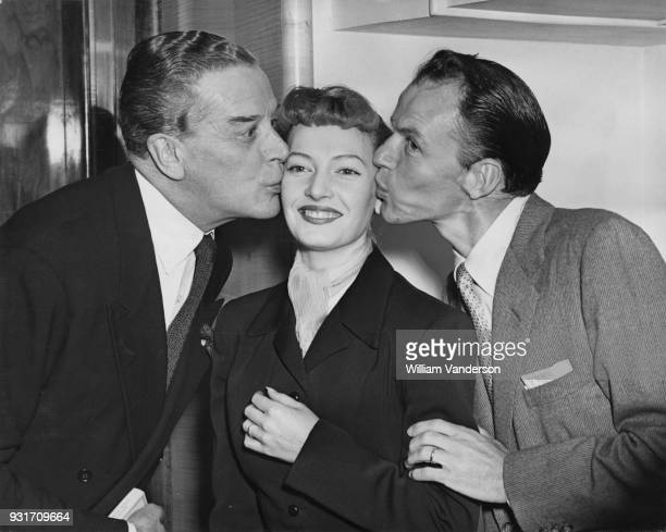 Englishborn actress singer and dancer Jeannie Carson receives a kiss from actors Jack Buchanan and Frank Sinatra during a Variety Club luncheon in...