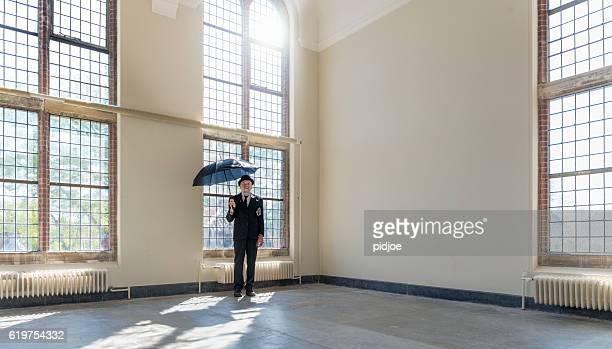 Englishman in bowler hat and open black umbrella.