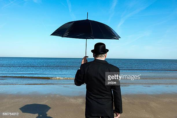 Englishman standing on the beach, overlooking the sea