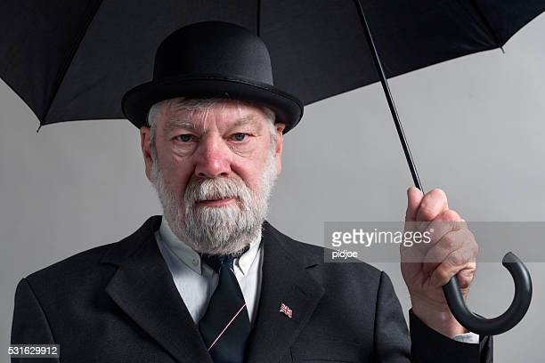 englishman with bowler hat and open black umbrella. - striped suit stock pictures, royalty-free photos & images