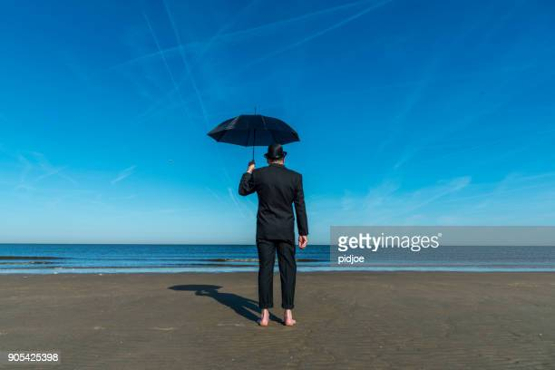 """Englishman with bowler hat and umbrella stands barefoot on the beach overlooking the sea and towards Europe.""""nConcept for the Brexit referendum."""