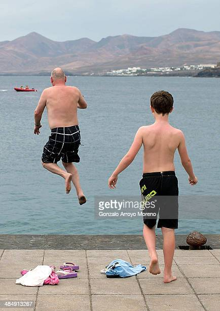 Englishspeaking tourists jump into the water at Puerto del Carmen quay on April 12 2014 in Lanzarote Spain Lanzarote where British Prime Minister...