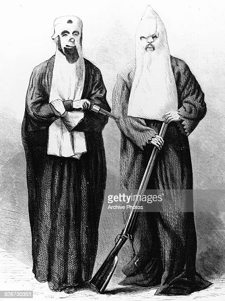 Engraved illustration depicting two members of the Klu Klux Klan wearing hoods and holding weapons circa 1860