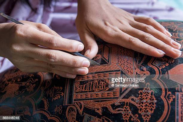 Engraving an oriental pattern on a lacquer vase