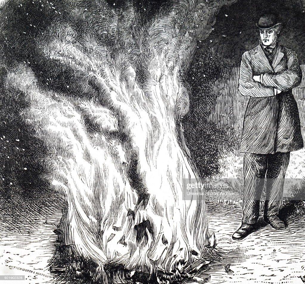 A man burning books on a bonfire. : News Photo