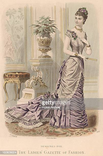 Engraving from 'The Ladies' Gazette of Fashion' depicting a woman wearing an ornate flowing gown with a closed fan in her hand circa 1875 By Lefranco