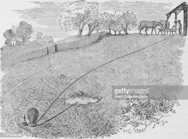 """Engraving of the man giveing water to his horses with the hose, from the book """"Industrial history of the United States"""" by Albert Sidney Bolles,..."""