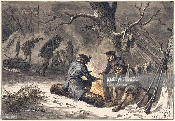 Engraving shows American troops as they warm themselves over a fire carry wood and camp at Valley Forge Pennsylvania December 1777 The Continental...