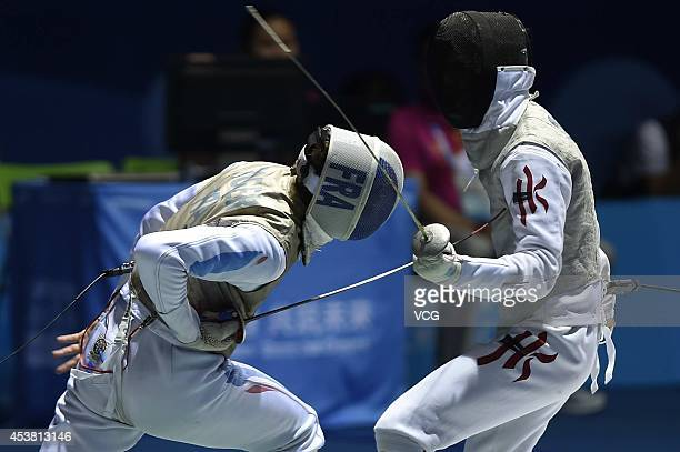 Enguerand Roger of France competes with Choi Chun Yin of Hong Kong in the Men's Foil Individual semifinal match on day three of the Nanjing 2014...